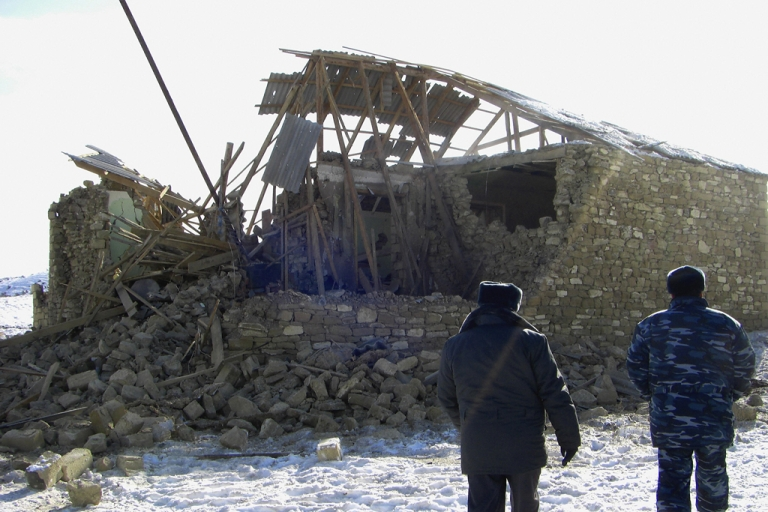 <p>Russian troops look at a destroyed house located in the turbulent Dagestan region of North Caucasus.</p>