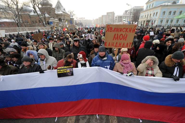 <p>People carry a Russian flag as they march in a anti-Putin rally in central Moscow, on February 4, 2012. The poster reads: