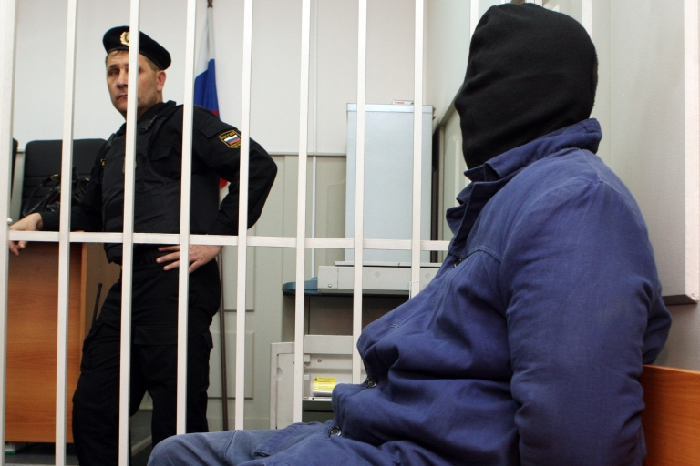 <p>Russian murder suspect Nikita Tikhonov, with a black bag over his head, sits in the defendant's cage of a Moscow court on Nov. 5, 2009. Two Russian nationalists, a man and a woman, Nikita Tikhonov and Yevgenia Khasis have been arrested and charged in the high-profile killings of human rights lawyer Stanislav Markelov and Anastasia Baburova, a reporter at opposition newspaper Novaya Gazeta, who were gunned down in Moscow in January.</p>