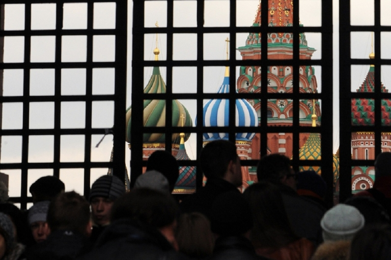 <p>Russian opposition activists stand behind the closed entrance to the Red Square in Moscow.  About 300 people were planning to hold a silent rally there, wearing their symbol: the white stripe.</p>