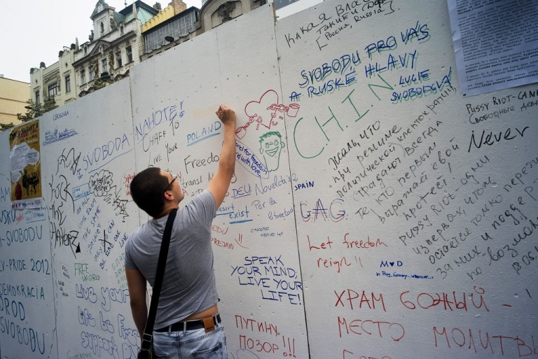 <p>A man writes on a wall dedicated to supporting the detained members of the Russian all-girl punk rock band 'Pussy Riot' in Prague, Czech Republic.</p>