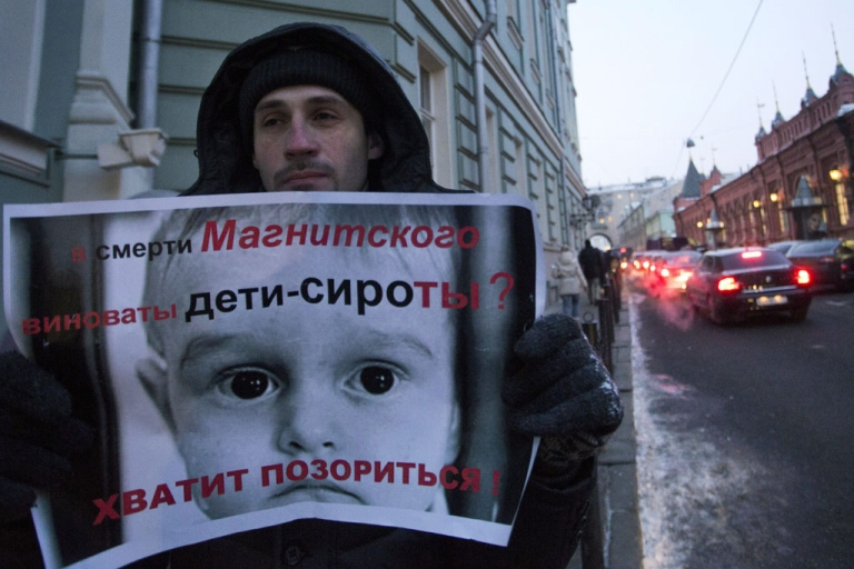 <p>A protester holds a poster which reads,