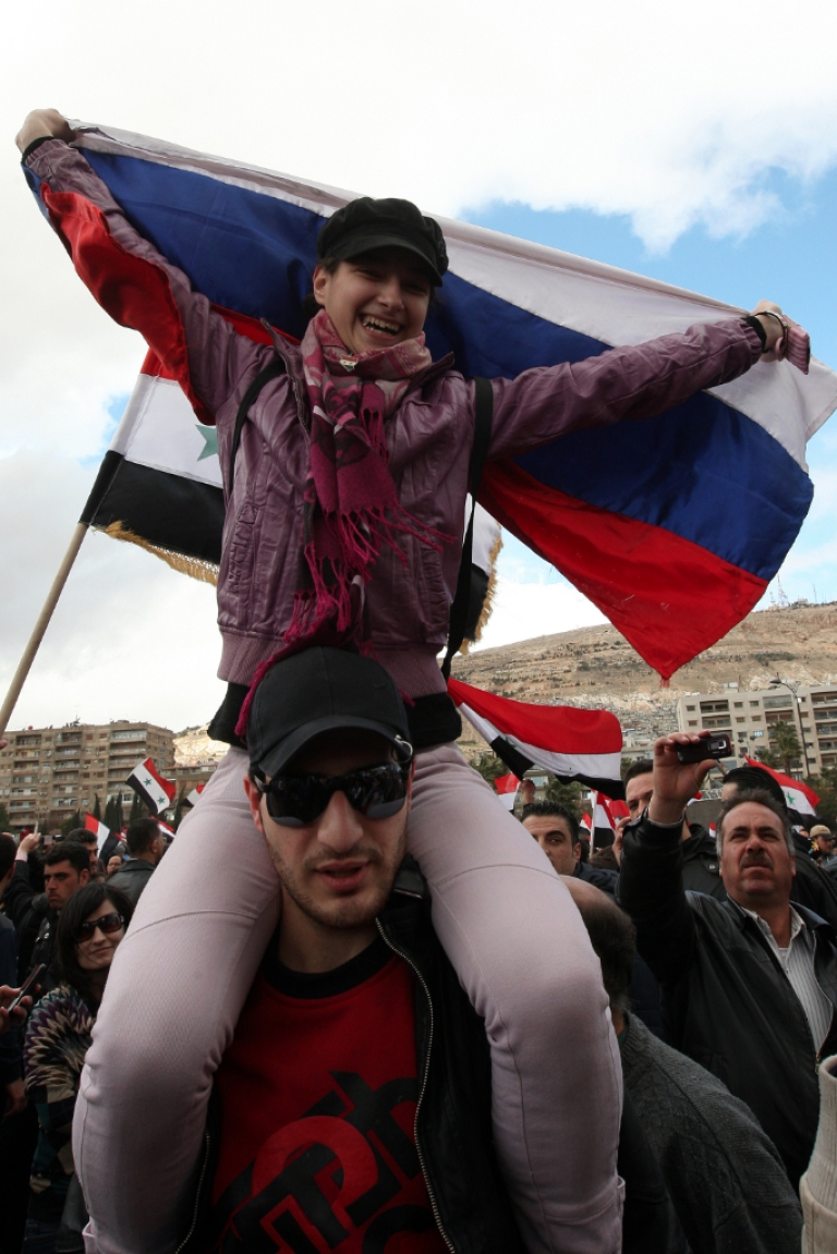 <p>A Syrian girl holds a Russian flag during a state-sponsored Damascus rally in support of President Bashar al-Assad on the first anniversary of the anti-government uprising on March 15, 2012.</p>