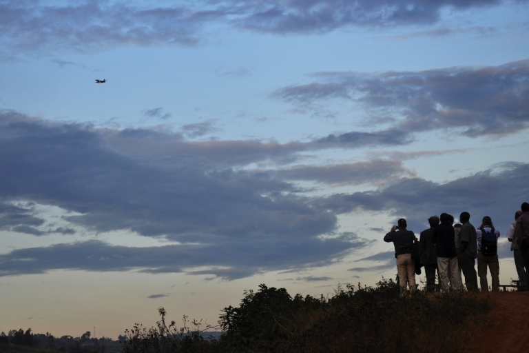 <p>A group of people watch as a plane makes it's final approach to the International airport in Kigali, Rwanda, on Sept. 16, 2010.</p>