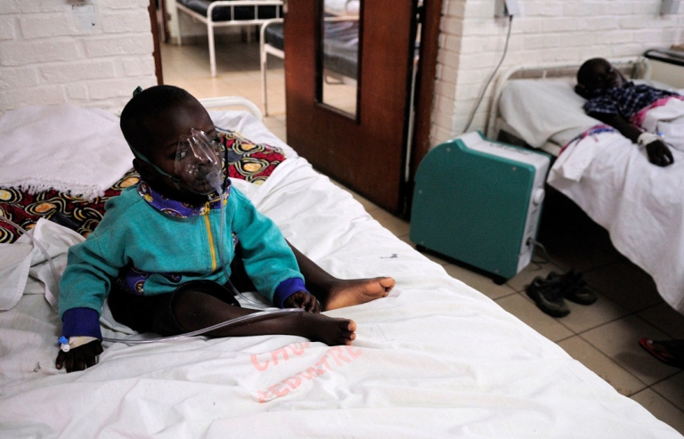 <p>Yves Twemerimana, 3, wears an oxygen mask in a bed at the Kigali Central University Hospital in Kigali, as he is tended to for a severe case of pneumonia.</p>