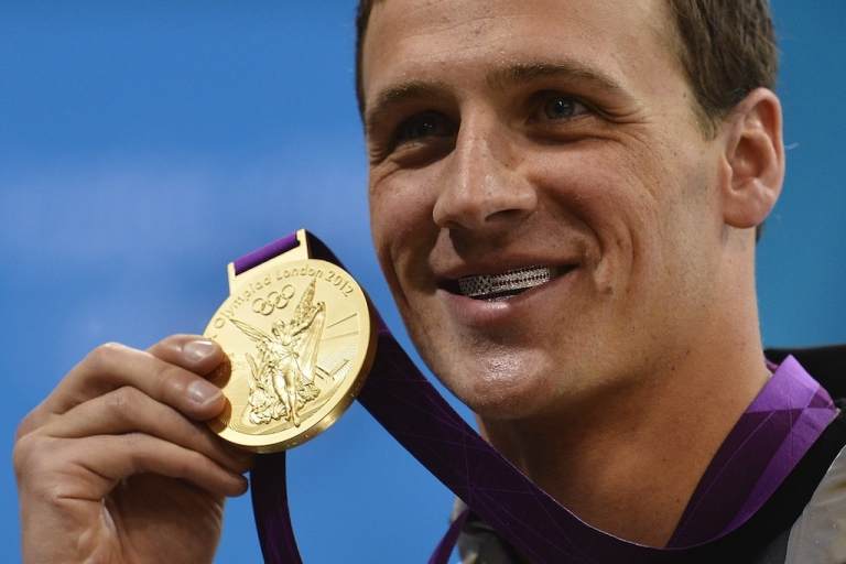 <p>US swimmer Ryan Lochte poses on the podium with his gold medal after winning the men's 400-meter individual medley swimming event at the London 2012 Olympic Games on July 28, 2012.</p>