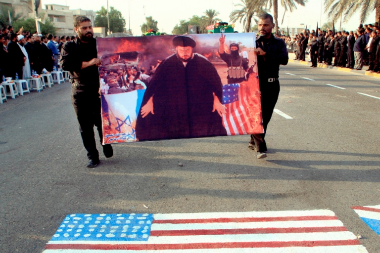 <p>Followers of radical Shiite cleric Moqtada al-Sadr hold up a poster of their leader as they march on a US flag during a 2007 rally in Basra, Iraq.</p>
