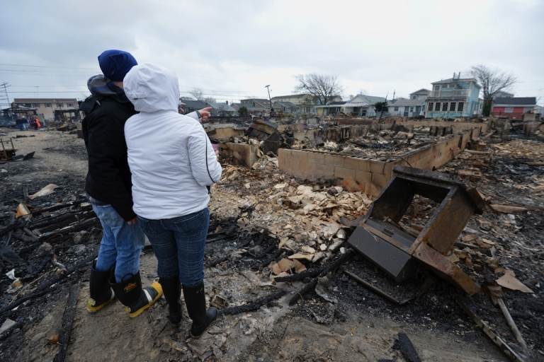 <p>People view damage in a neighborhood in the Breezy Point area of Queens in New York on October 30, 2012 after fire destroyed about 80 homes as a result of Hurricane Sandy which hit the area October 29.</p>