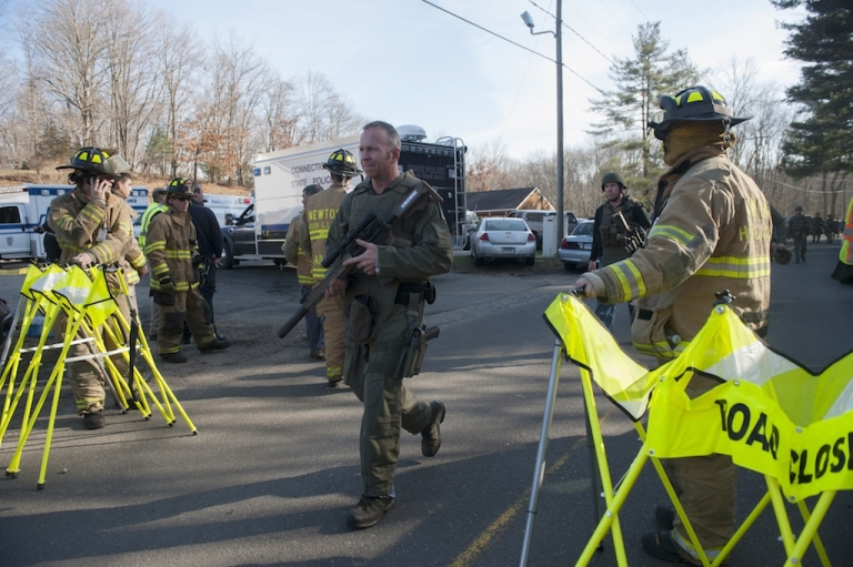 <p>Connecticut State Police walk near the scene of an elementary school shooting on December 14, 2012 in Newtown, Connecticut.</p>