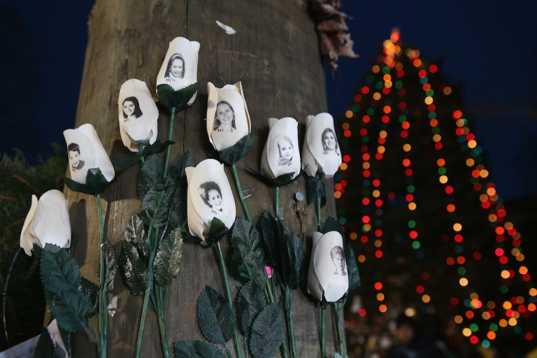 <p>White roses with photos of victims of last Friday's mass shooting hang at a streetside memorial in Newtown, Connecticut.</p>