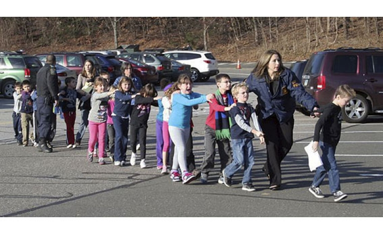 <p>In this photo provided by the Newtown Bee, Connecticut State Police lead children from the Sandy Hook Elementary School in Newtown, Conn., on Friday, Dec. 14, 2012.<br /> Photograph by Shannon Hicks, Newtown Bee.</p>