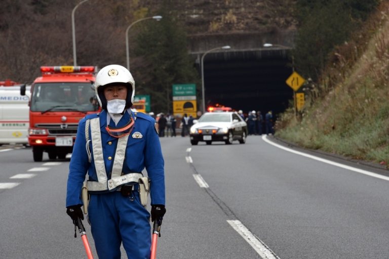 <p>A policeman stands guard in front of the entrance of the collapsed Sasago tunnel on the Chuo expressway in Koshu city, Yamanashi prefecture, on Dec. 2, 2012. Nine people were killed in the collapse and subsequent fire.</p>
