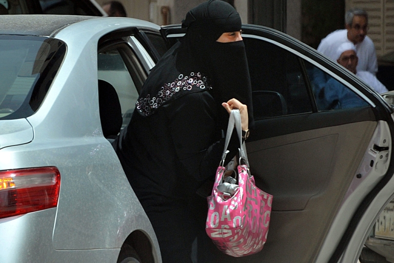 <p>A Saudi woman gets out of a car after being given a ride by her driver in Riyadh.</p>