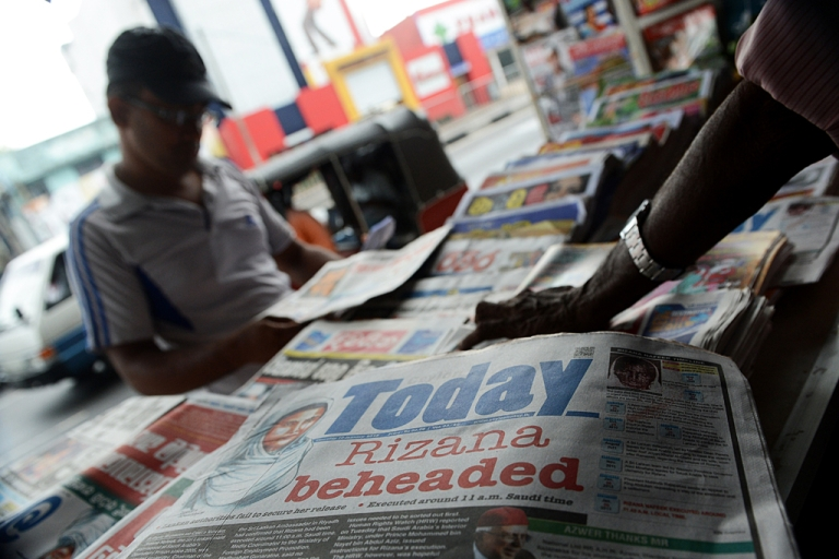 <p>A Sri Lankan vendor displays the front page of daily newspapers in Colombo on Jan. 10, 2013.</p>