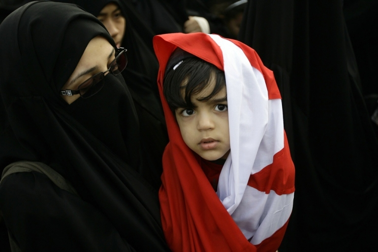 <p>A Bahraini girl wrapped in her national flag takes part in an anti-regime rally at Pearl Square, the focal point of demonstrations in Manama, on March 1, 2011.</p>