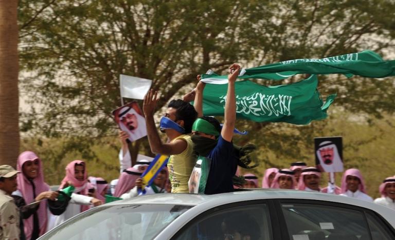 <p>Saudi youth wave their national flag as they celebrate the return of King Abdullah bin Abdul Aziz in the Saudi capital Riyadh on Feb. 23, 2011.</p>