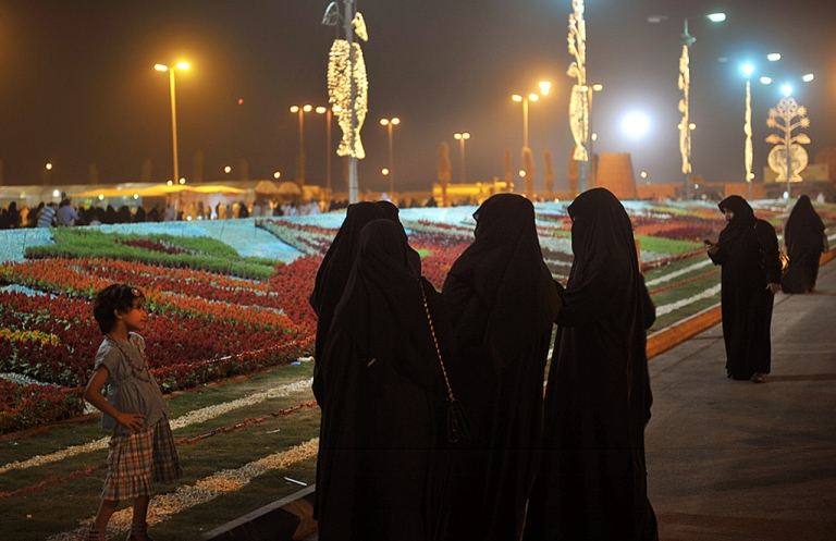 <p>Saudi women gather in front of a carpet made of over 135,000 flowers at the Riyadh Spring Festival in the Saudi capital on April 15, 2011.</p>