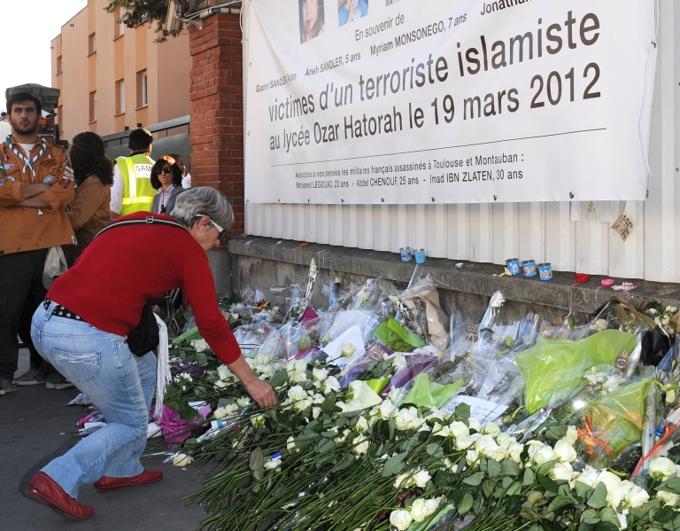 <p>At the end of a march by people from all faiths on Sunday, a woman lays a white rose in front of the Ozar Hatorah Jewish school in the southwestern city of Toulouse, where three children and one teacher were killed last week by self-proclaimed Islamist Mohamed Merah.</p>