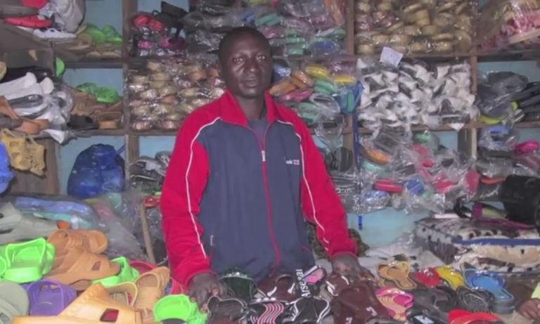 <p>A screen shot of a man surrounded by shoes from the A Day Without Dignity video.</p>