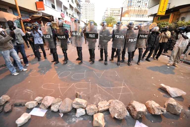 <p>Text written on the ground in chalk reads 'Down with the police' as riot policemen stand guard, blocking access to Independence Square during an opposition demonstration against Senegal's President Abdoulaye Wade's controversial bid for a third term, on Feb. 23, 2012, in Dakar.</p>