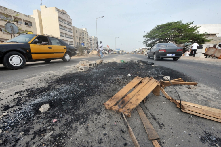 <p>In Dakar cars drive past a barricade erected during anti-government protests.</p>