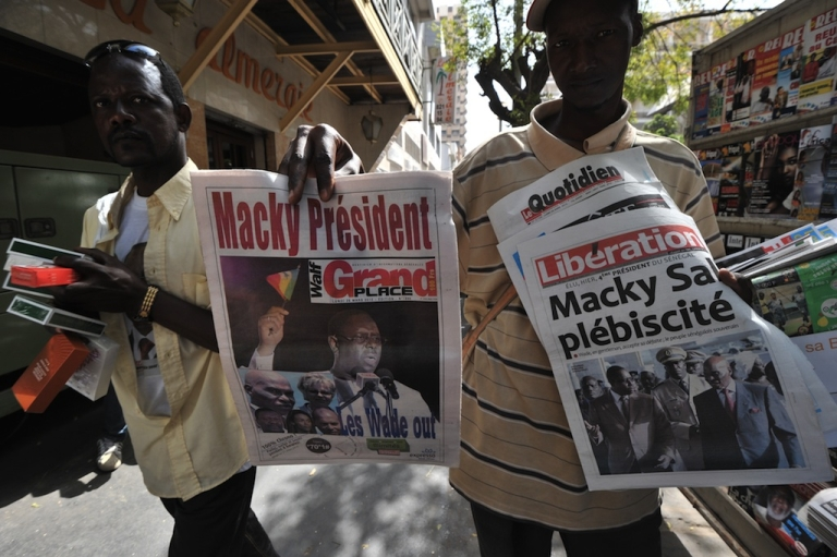 <p>A street vendor sells Senegalese newspapers commenting March 25's presidential elections on March 26, 2012 in Dakar. The African Union today praised the peaceful handover of power following presidential elections in Senegal, after incumbent Abdoulaye Wade's acceptance of defeat.</p>