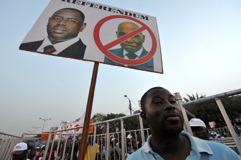 <p>A supporter of Senegalese opposition candidate Macky Sall holds a placard depicting a portrait of his candidate (L) and a barred one of incumbent President Abdoulaye Wade on March 12, 2012 in Dakar. Senegal's opposition joined forces today in a mass rally to block 85-year-old President Abdoulaye Wade from landing a third term in office.</p>