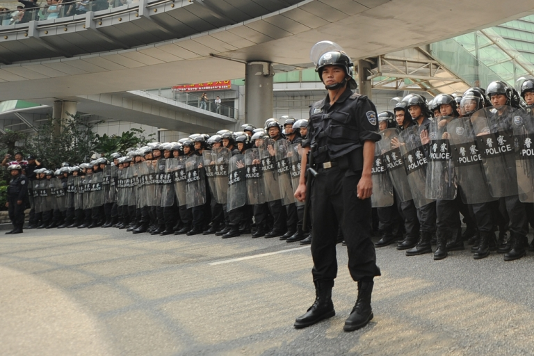 <p>Riot police stand guard as anti-Japan protesters march during a protest over the Diaoyu islands issue, known as the Senkaku islands in Japan, in the southern Chinese city of Shenzhen on September 18, 2012. Thousands of anti-Japan protesters rallied across China over a territorial row on a key historical anniversary, as Japanese firms including car giant Toyota shut or scaled back production in across the country.</p>