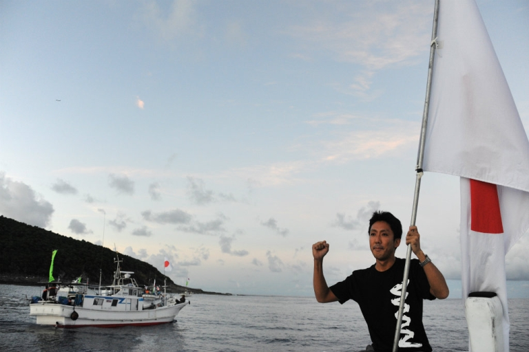 <p>An activist holds the Japanese flag before a group placed the country's flag on a disputed island, part of a group known as Senkaku in Japanese and Diaoyu in Chinese. China announced Saturday that it was creating an air defence zone around the islands to the dismay of Japan.</p>