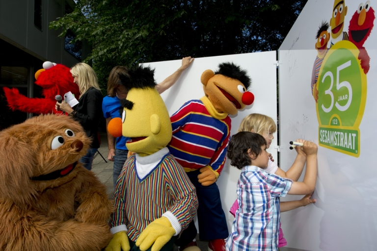 <p>Children sign a wall as they mark the 35th anniversary of Sesame Street flanked by characters Elmo, Tommie, Bert and Ernie at the Dalton School in Amsterdam, on July 20, 2011.</p>