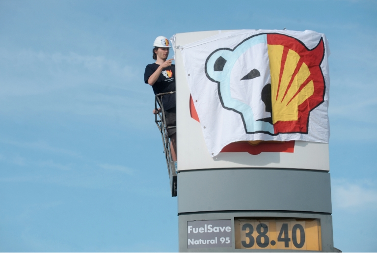 <p>A Greenpeace environmental activist covers the logo of the Shell oil company to protest the company's oil drilling project in the north of Alaska on May 10, 2012.</p>