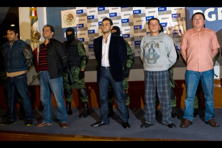 <p>Vicente Zambada Niebla, aka 'El Vicentillo', stands at center amongst other criminals after his arrest in Mexico City in March 2009.</p>