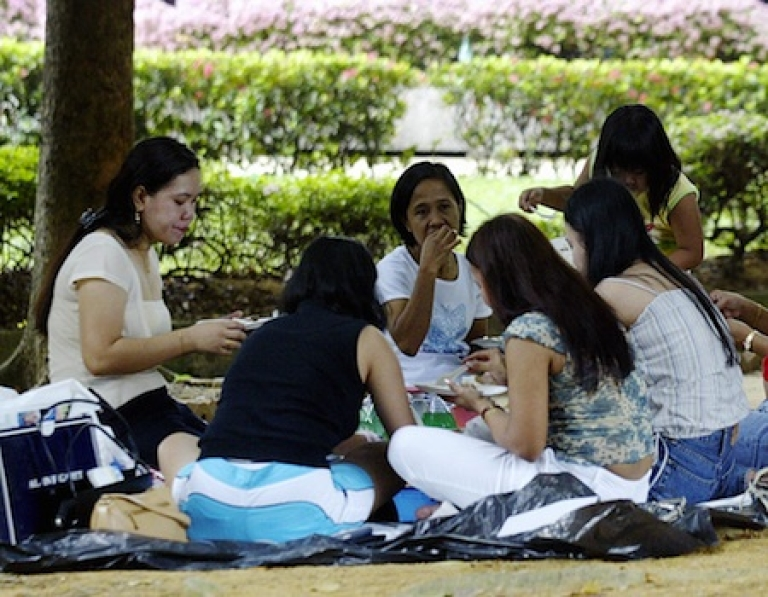 <p>Domestic helpers enjoy a picnic in the shade at 'Gulung-gulung' park in Singapore.</p>