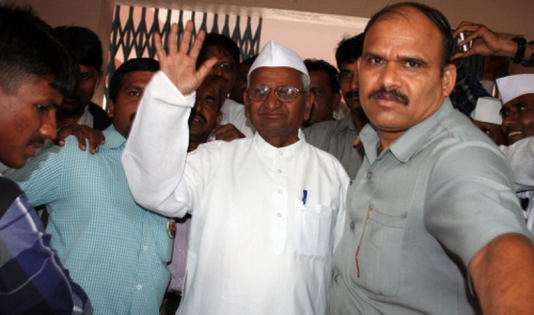 <p>Anna Hazare (C), the Indian anti-corruption activist whose 13-day fast forced the government to reconsider a new law tackling graft, waves to supporters in his village of Ralegan Siddhi on September 2, 2011.</p>