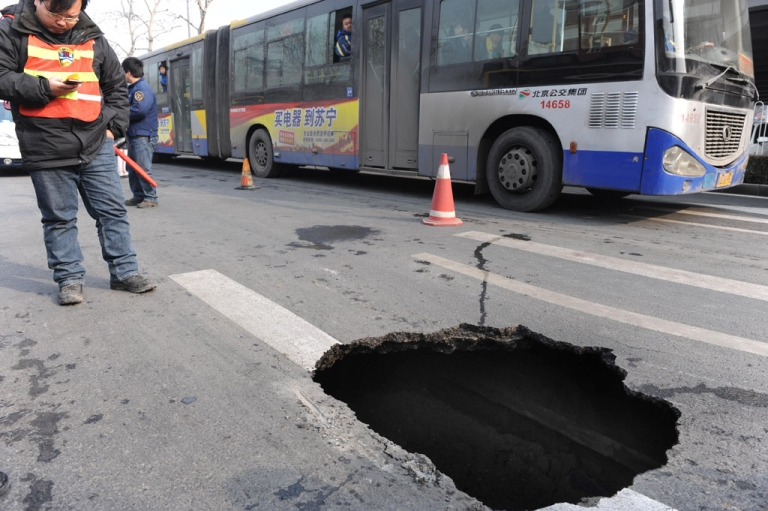 <p>A Chinese worker inspects a sinkhole in a street in Beijing. A Russian toddler fell to his death in a similar sinkhole on Sunday.</p>