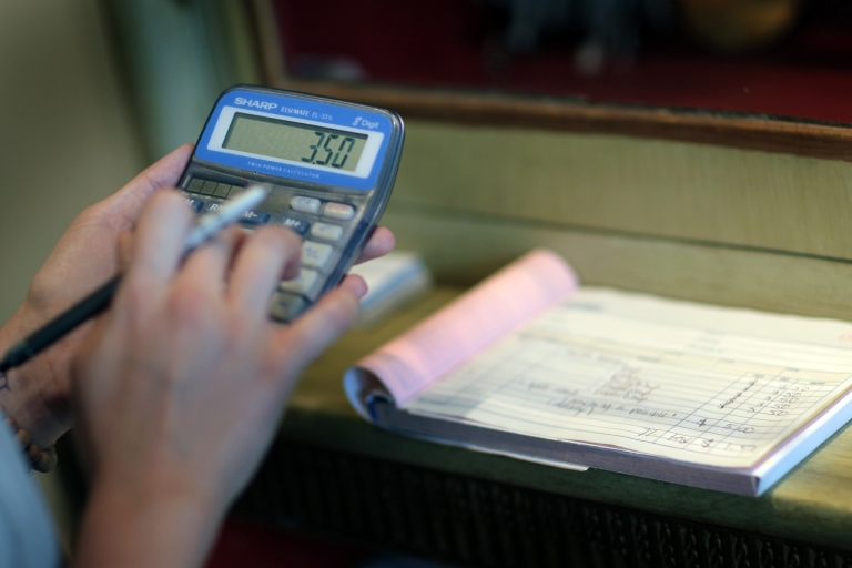 <p>A salesperson at the Design Box, a home boutique in Miami, calculates a sale on Sept. 14, 2010.</p>