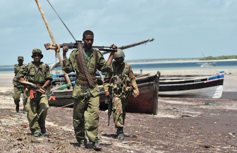 <p>Militia allied with the Federal Government of Somalia and Kenyan Defence Force soldiers walk along the coast near Burgabo village, Southern Somalia on December 14, 2011. Burgabo is a Somalian port village which has been secured by Kenyan forces as they advance further up the Somali coastline in search of Al-Shabaab fighters.</p>