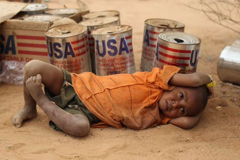 <p>A young Somali refugee rests by empty vegetable oil tins delivered by USAID to the Dadaab refugee camp in Kenya. The boy is seen on July 20, 2011 at the Dagahaley refugee settlement inside Dadaab.</p>