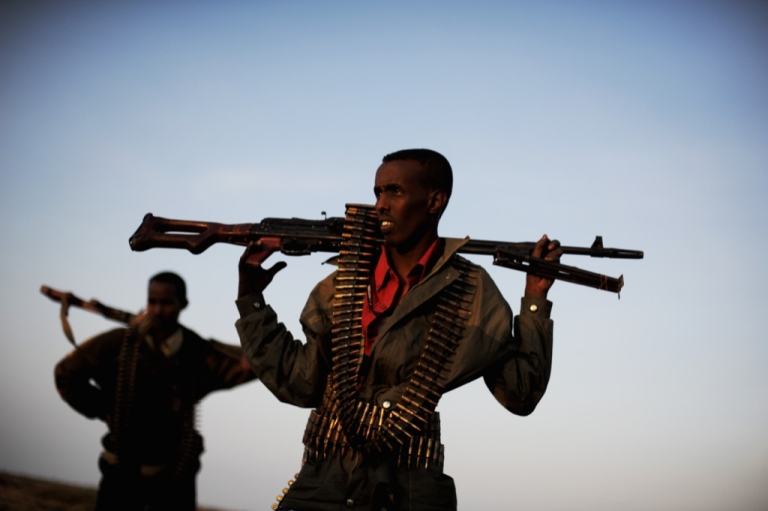 <p>Men providing security for a local official hold their weapons as they stand in a field in the plains near the central Somali town of Galkayo on Aug. 18, 2010.</p>