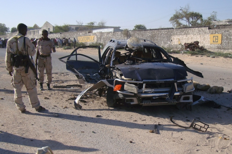 <p>Soldiers stand next to a car bomb that exploded near a military base housing Burundian soldiers from an African Union peacekeeping force in the Hodan district of Mogadishu on March 3, 2012 . Another car bomb was detonated in Somalia's capital on March 21, 2012.</p>