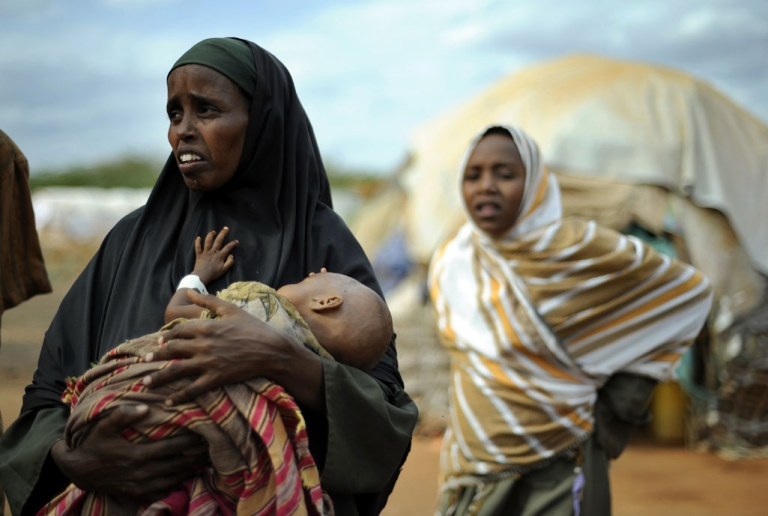 <p>A displaced Somali refugee cradles her severely emaciated child at the Dadaab Refugee camp, in eastern Kenya, where around 1,500 people are arriving every day in search of food, water and medical care.</p>