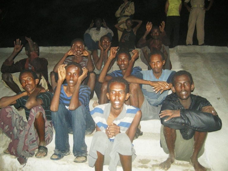 <p>Somali pirates get their own movie. Here, suspected Somali pirates that arrived on the coast of Dwarka by boat sit on the ground as they are guarded by marine reserve police in Jamnagar district in Gujarat state on June 26, 2011. Indian police detained 18 suspected Somali pirates.</p>