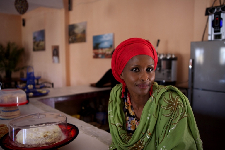 <p>British-Somali woman Ayan Hussein stands behind the counter at her newly opened Kulan Art Cafe in Hargeisa.</p>