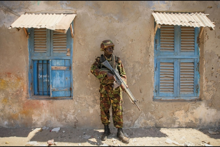 <p>A soldier of the Kenyan Contingent serving with the African Union Mission in Somalia (AMISOM) stands guard on a street in the centre of the southern Somali port city of Kismayo while a combat engineering team inspects the surrounding area following reports of a suspected improvised explosive device (IED) left behind by the Al-Qaeda-affiliated extremist group Al Shabaab.</p>