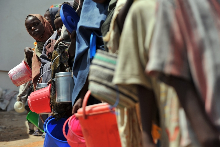 <p>Displaced Somali children queue as they wait for food-aid rations on Jan. 19, 2012 at a distribution centre in Mogadishu. Famine conditions have ended in war-torn Somalia six months after they were declared, but the situation remains dire with a third of the population needing emergency aid.</p>