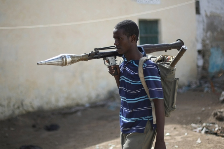 <p>An Al-Shabab Islamic fighter, wearing a rock launcher, walk at a front line section in sanca district in Mogadishu.</p>