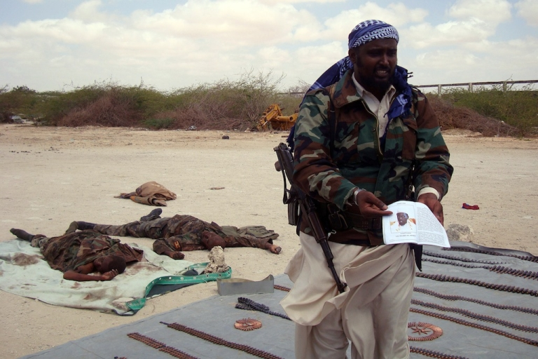 <p>An ex-US soldier tried to join Somalia's Al Shabaab militants. Here, a spokesman of the Al Qaeda-linked militants in Somalia, Sheik Ali Mohamud Rage holds a picture of Somalia President Sharif Sheik Ahmed during a display of the bodies of two alleged Ugandan soldiers they claimed to have killed during clashes in Mogadishu on February 20, 2011. The African Union mission in Somalia (AMISOM) said the fighting was triggered by its discovery of a mile-long trench system used by the Al Qaeda-inspired Al Shabaab insurgents in the capital.</p>