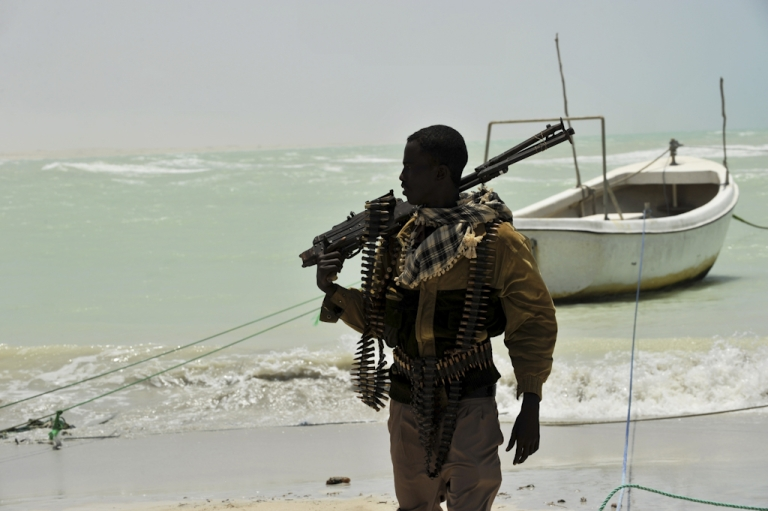 <p>A Somali man, part armed militia, part pirate, carries his high-caliber weapon on a beach in the central Somali town of Hobyo.</p>