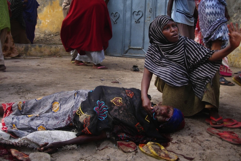 <p>A woman crouches beside another person who was severely injured by a road side bomb in Mogadishu on Aug. 3, 2008.</p>