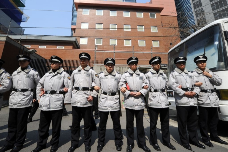 <p>Policemen stand guard in front of the Japanese embassy as South Korean protesters hold a rally against new Japanese textbooks in Seoul on March 30, 2011.</p>